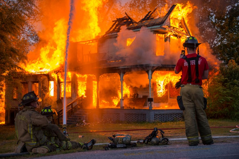 A firefighter standing in front of a house on fire
